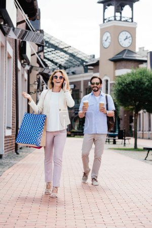 wife talking by smartphone and holding shopping bags, husband carrying disposable coffee cups on street