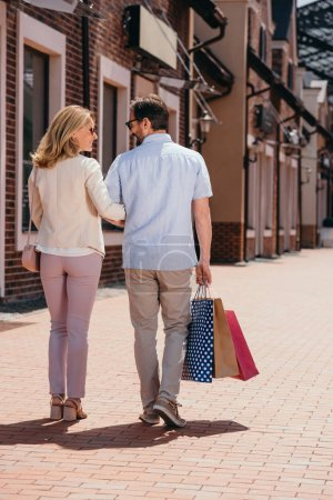 back view of couple walking with shopping bags on street
