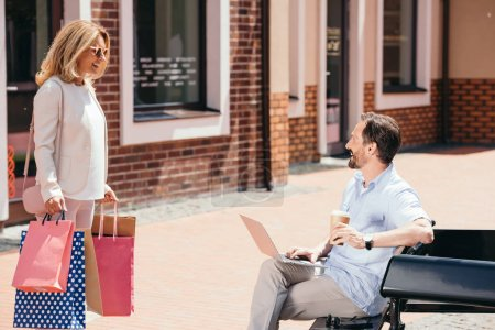 handsome man sitting on bench with laptop and woman standing with shopping bags