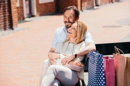 Photo pour Couple heureux hugging sur banc après le shopping - image libre de droit