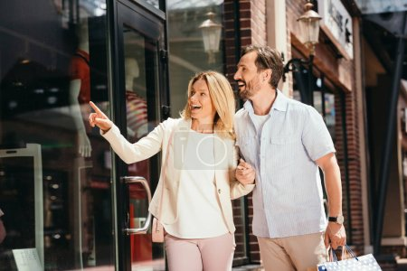 woman pointing on store showcase from street