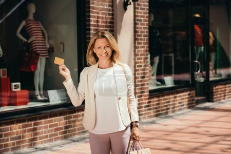 attractive woman holding credit card and shopping bags on street