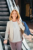 smiling attractive woman standing on escalator with shopping bags in mall