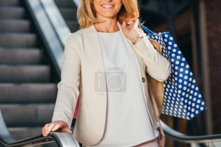Photo pour Cropped image de femme souriante debout sur l'escalier roulant avec des sacs de shopping au centre commercial - image libre de droit