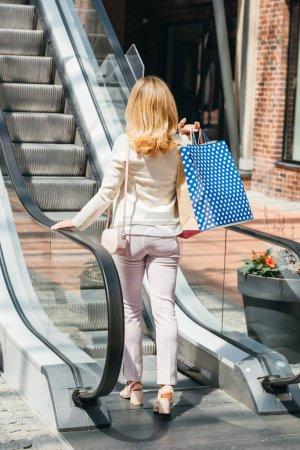 Photo pour Vue arrière du femme marchant sur l'escalier roulant avec des sacs de shopping au centre commercial - image libre de droit