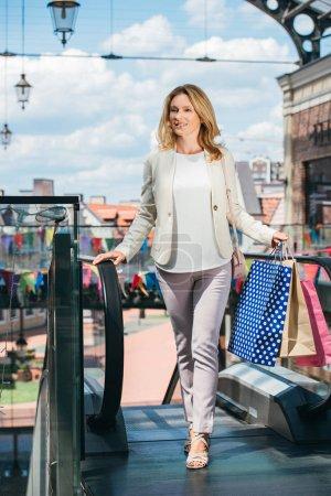 beautiful woman walking with shopping bags in mall