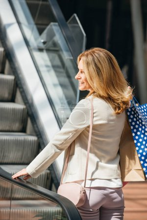 side view of attractive woman on escalator with paper bags