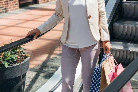 Photo pour Cropped image de femme sur moving escalier avec des sacs de shopping au centre commercial - image libre de droit