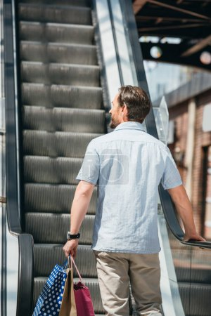 back view of man standing on escalator with shopping bags in mall