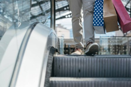 cropped image of man stepping on escalator in shopping mall