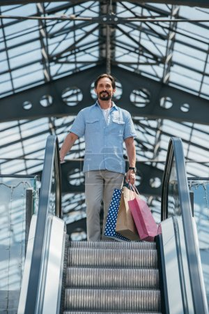 Photo for Low angle view of handsome man standing on escalator with shopping bags - Royalty Free Image
