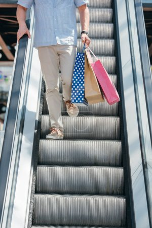 cropped image of man walking on escalator with shopping nags