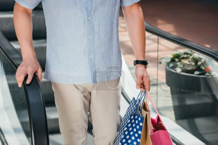 cropped image of man standing on moving staircase with shopping bags