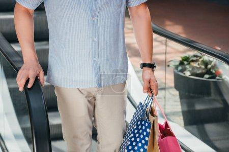 Photo pour Image recadrée de l'homme debout sur moving escalier avec des sacs à provisions - image libre de droit