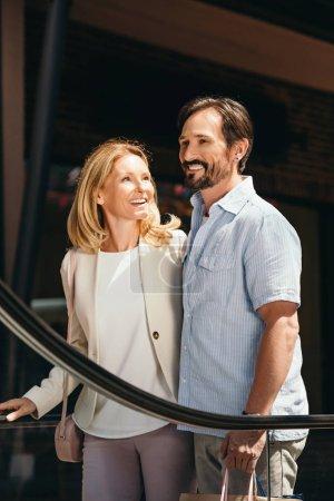 Photo pour Couple souriant sur moving escalier dans centre commercial - image libre de droit