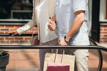 Photo pour Image recadrée de couple sur moving escalier dans centre commercial - image libre de droit