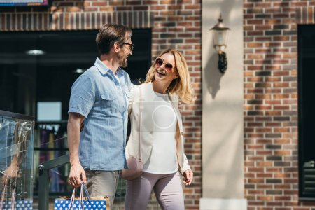 Photo for Smiling couple in sunglasses walking with shopping bags - Royalty Free Image