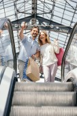 low angle view of couple looking at something in shopping mall from escalator