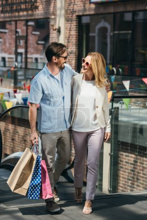 Photo for Happy couple in sunglasses hugging in shopping mall - Royalty Free Image