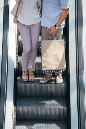 Photo pour Cropped image du couple se tenant debout sur escalator avec sacs à provisions - image libre de droit
