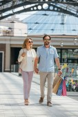 happy couple in sunglasses holding hands and walking in shopping mall