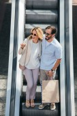 high angle view of happy couple in sunglasses looking away on escalator in shopping mall