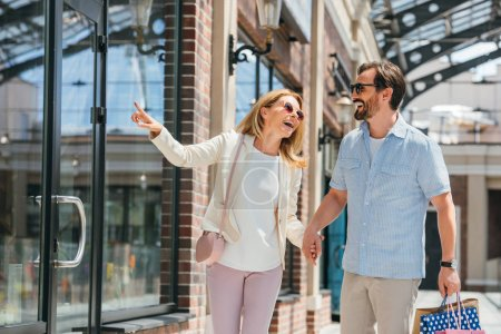 Photo for Happy wife pointing on something to husband in shopping mall - Royalty Free Image