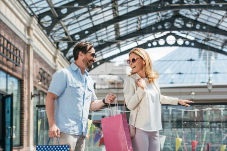 Photo for Happy couple in sunglasses looking at each other in shopping mall - Royalty Free Image