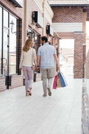 Photo pour Vue arrière du couple tenant la main et marchant avec des sacs à provisions - image libre de droit