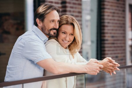 Photo for Happy couple hugging on balcony and looking away - Royalty Free Image