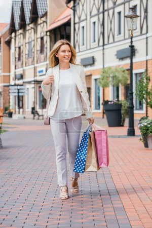 Photo for Attractive stylish woman walking with shopping bags on street - Royalty Free Image