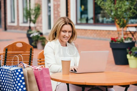 Photo for Attractive woman working with laptop at table in cafe - Royalty Free Image