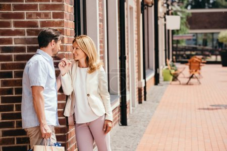 Photo pour Affectueux couple main dans la main et en regardant l'autre sur rue dans la ville - image libre de droit
