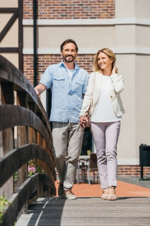 Photo for Couple holding hands and walking on bridge - Royalty Free Image