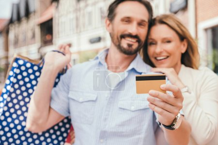 Photo for Couple hugging and holding shopping bags with credit card on foreground - Royalty Free Image