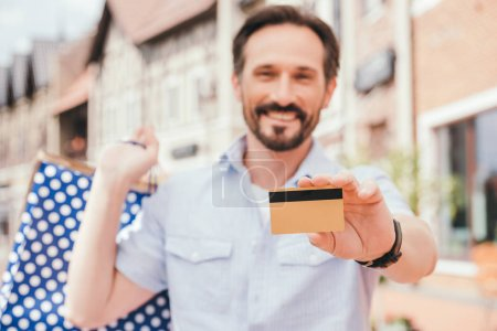 smiling handsome man showing credit card