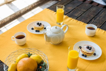 close up view of pancakes, cups of tea and glasses of juice for breakfast on table with yellow tablecloth