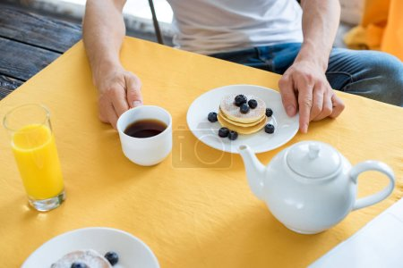 Photo for Partial view of man sitting at table with breakfast at home - Royalty Free Image