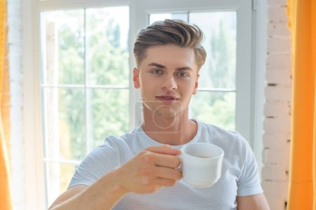 Photo for Portrait of young man with cup of tea looking at camera at home - Royalty Free Image