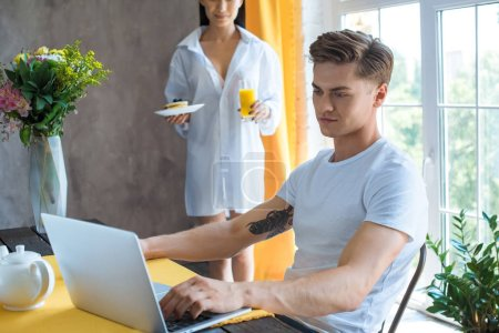 Photo for Selective focus of woman brought breakfast to boyfriend at table with laptop at home - Royalty Free Image
