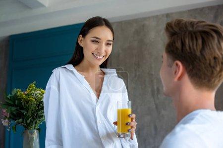 Photo pour Foyer sélectif de sourire asiatique femme avec verre de jus de regarder copain à la maison - image libre de droit
