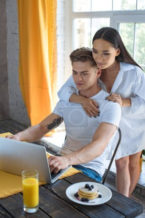 smiling asian woman hugging caucasian boyfriend at table with laptop and breakfast at home
