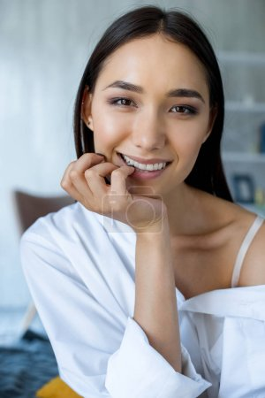 portrait of beautiful smiling asian woman looking at camera at home