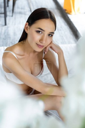 portrait of attractive asian woman in underwear looking at camera on bed