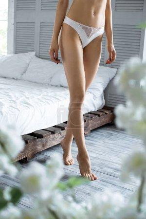 partial view of woman in underwear in bedroom