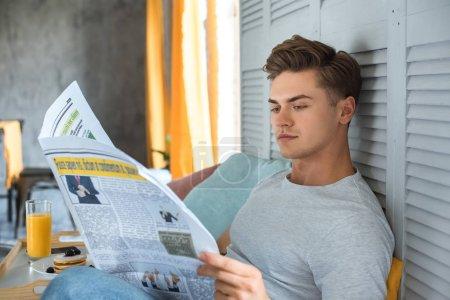 Photo pour Vue latérale du jeune homme lisant le journal au lit le matin - image libre de droit