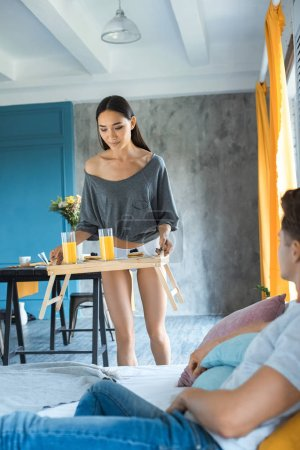 selective focus of asian woman brought breakfast to caucasian boyfriend in bed at home