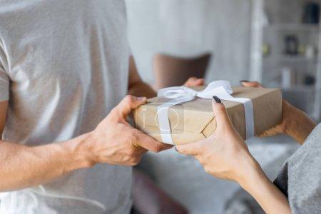 Photo pour Vue partielle de l'homme présentant cadeau emballé à la petite amie à la maison - image libre de droit