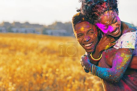 laughing african american couple piggybacking at holi festival in wheat field