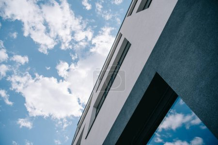 low angle view of building against cloudy bright blue sky